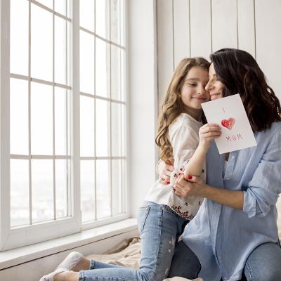 Máma s dcerou se objímají, dcera drží přání se srdcem. Jsou v sedu v interiéru u velkého okna.